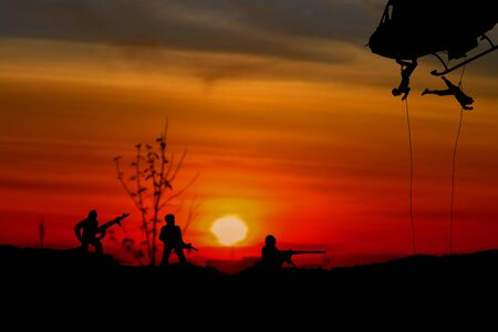 Silhouette Soldiers rappel down to attack from helicopter with warrior beware danger On the ground sunset Background blur and copy space add text