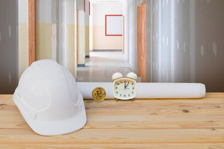 white safety helmet plastic, paper roll plan blueprint alarm clock time a rest at noon, bitcoin coin on wood floor table and gypsum board wall interior construction site background. with copy space add text