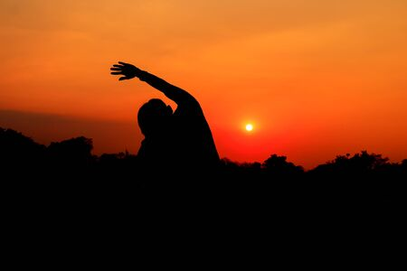 Silhouette of male meditating and yoga practicing with exercise at sunrise in public park morning Stock Photo