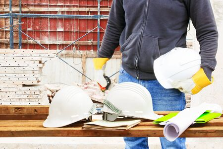 engineer hand holding white safety hat and paper plan blueprint on wood table in working construction site housing building with copy space add text
