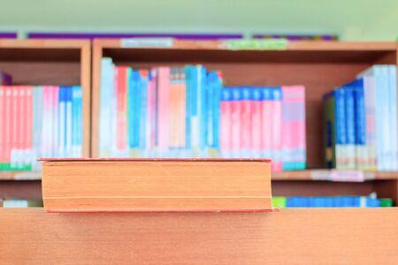 altes Buch rot in der Schulbibliothek auf Holztisch. verschwommene Bücherregale Hintergrund. Bildungslernkonzept mit Kopienraum Text hinzufügen