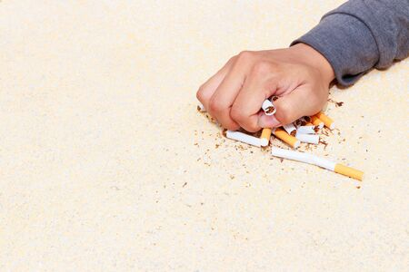 male hand crushed pile cigarettes Close up on table terrazzo flooring yellow background. health care concept stop quitting smoking.