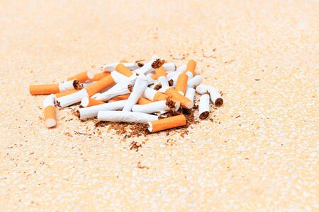Pile cigarettes broken on table terrazzo flooring yellow background. health care concept stop quitting smoking. Stock fotó