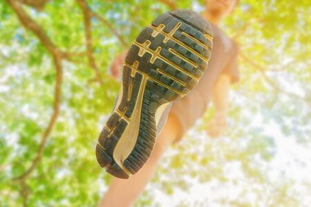 running feet male view from below in runner jogging exercise with old shoes in public park for health lose weight concept. copy space add text