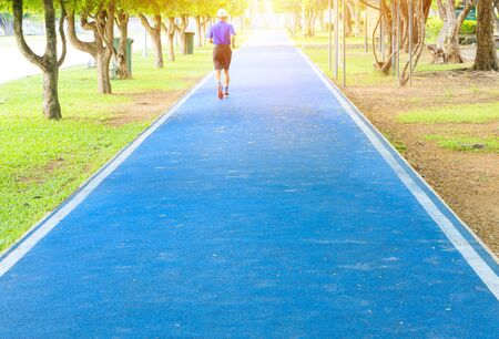 elderly people motion running feet in runner jogging exercise for health lose weight concept on track rubber cover blue public park. copy space add text, select focus with shallow depth of field.
