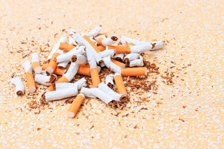 Pile cigarettes broken on table terrazzo flooring yellow background. health care concept stop quitting smoking.
