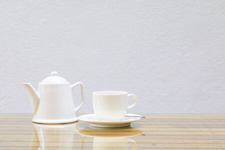 coffee cup and teapot white On the glass table wooden and a cement wall background. copy space