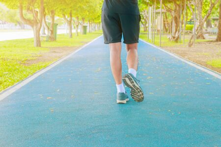 running feet male in runner jogging exercise with old shoes for health lose weight concept on track rubber cover blue public park. copy space add text