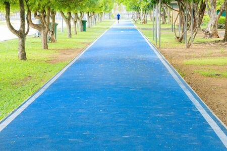 running track in runner rubber cover blue public park. for jogging exercise health lose weight concept copy space add text, select focus with shallow depth of field.