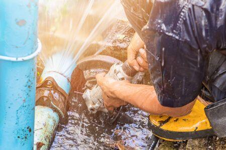 plombier travaillant réparer le tuyau cassé et remplacer dans le trou avec de l'eau Mouvement au bord de la route
