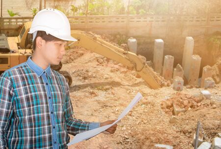 Engineer open hold blueprints in Construction site concept Blurred background