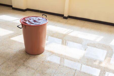 water leak drop interior office building in red bucket from Ceiling and flow on terrazzo floor Reklamní fotografie