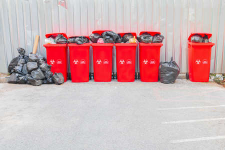 group red bins six with symbol infectious and garbage bag black pile On top in the outdoors. concept prevent infection coronavirus (covid-19)