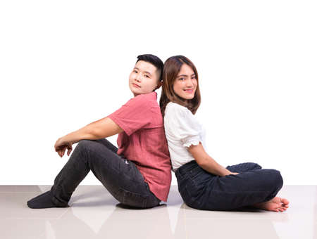Two smiling woman young girls and happiness tomboy friends sitting back to back on tile floor in home with white background