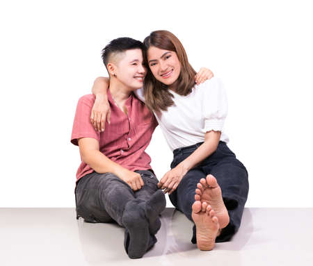 Two smiling woman young girls and happiness tomboy friends sitting on tile floor with white background