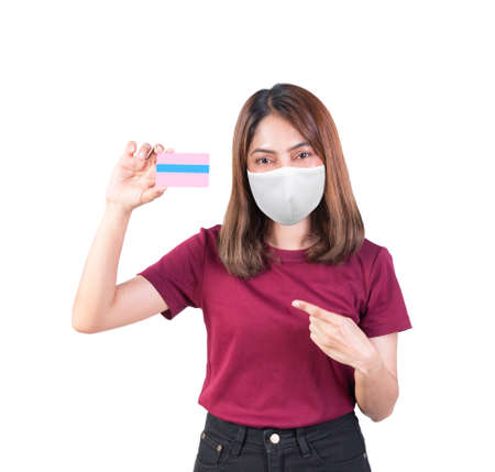 woman holding credit card Pointing finger and wearing fabric mask safety Covid-19 or on white background Archivio Fotografico