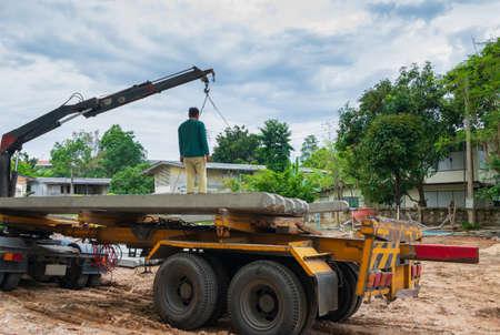 pile concrete pillars on trailer truck in construction site