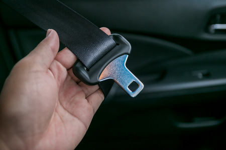 fastening: transportation and vehicle concept - man fastening seat belt in car
