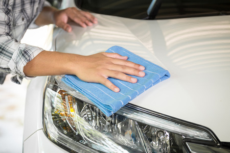 hand rubbing: A man cleaning car with microfiber cloth, car detailing (or valeting) concept