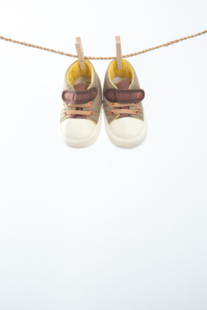 sully: Baby shoes hanging on a rail junction on the white background.