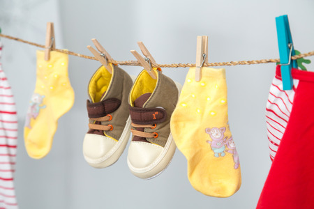 sully: Baby clothes hanging on the rack isolated on white background. Stock Photo