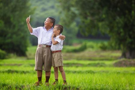 Gelukkig kind neem een selfie in het korenveld, aziatische