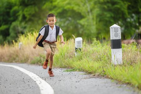 幸せな小さな男の子が学校から家に帰る 写真素材
