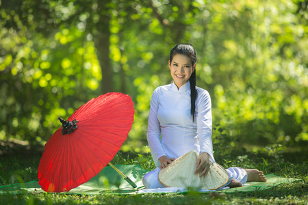 Pretty girl in Vietnam, sitting on a mat with a red umbrella. Stockfoto