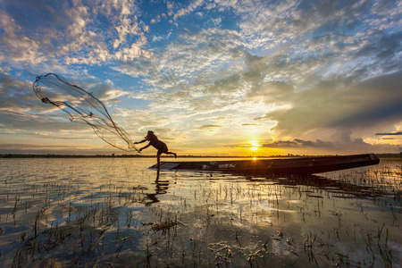 Asian fisherman on wooden boat casting a net for catching freshwater fish in nature river in the early morning before sunrise Stockfoto
