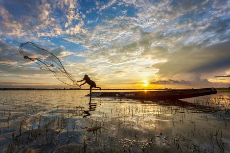 Aziatische visser op houten boot, werpende het net voor het vangen van zoetwatervissen in de natuur rivier in de vroege ochtend voor zonsopgang