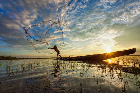 Asian fisherman on wooden boat casting a net for catching freshwater fish in nature river in the early morning before sunrise Stock Photo
