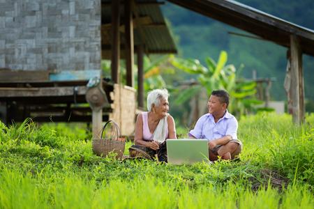 disadvantaged: grandmother and grandchildren play computer, asia