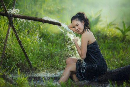 relaxion: beautiful young woman takes bath naturally flows from the bamboo chute.