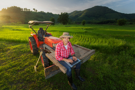 Young Farmer recorded growth of productivity sitting on a tractor in the background a rice paddy fields, mountains and sky.