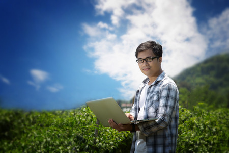 Attractive young farmers with a laptop sitting in a garden survey pepper.