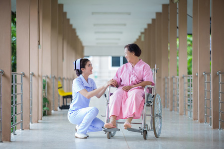 levantandose: young female caregiver helping senior woman getting up
