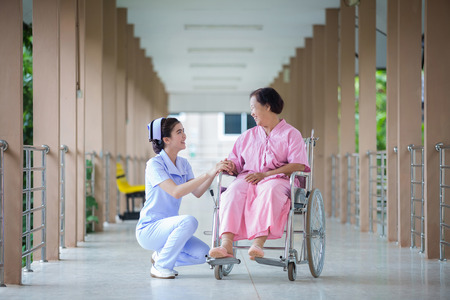 care giver: young female caregiver helping senior woman getting up