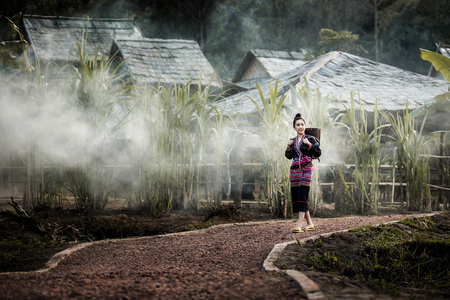 Black Hmong minority women who are about to walk through the village to the woods near the village, Laos.