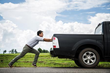 Man pushing a broken car down the road 스톡 콘텐츠