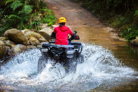 Het meisje rijdt een ATV door de rivier de Spree. Stockfoto