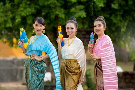 Asian girl playing a gun on Songkran festival.