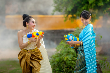 Asian woman playing guns in the Songkran Festival fun. Banco de Imagens