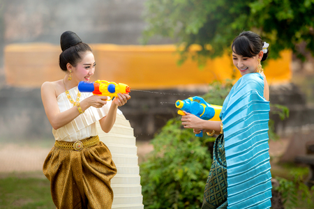 アジアの女の子は、ソンクラン祭りで銃を再生します。