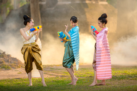 Asian girl playing a gun on Songkran festival.