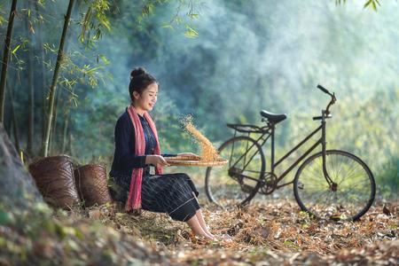 Beautiful Asian women winnowing grain with a happy smile.