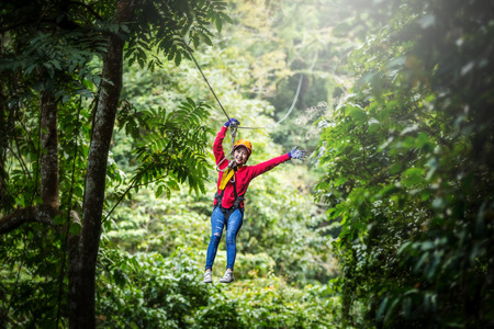 Woman going on a jungle zip line adventure, asia