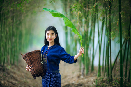 Beautiful asian woman carrying a basket and banana leaf looking forward hopefully.