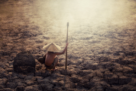 Asian sad a boy sitting on dry ground .concept hope and drought Stock Photo