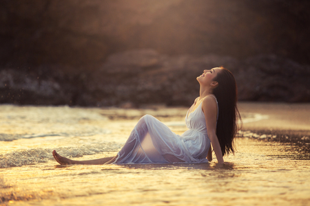 Asian girl sitting on a tropical beach by the sea to enjoy the sea breeze happily near the sunset. Stock Photo