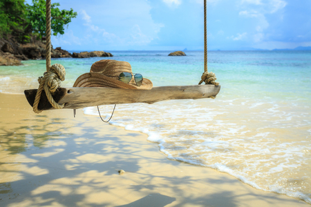 Swing hanging under the tree at mai-ton island, Phuket, Thailand , hat on swing, glasses, beach Stok Fotoğraf
